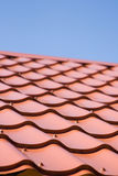 Red roof of metal roofing on the sky. Background stock photo