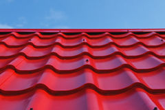 Red roof. From a metal tile on a blue sky background Royalty Free Stock Photos