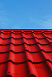 Red roof. From a metal tile on a blue sky background Stock Photography