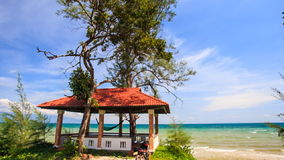 Red Roof Pavilion with Hammock on Beach against Azure Sea. Beautiful red roof pavilion with hammock on green lawn on beach against azure sea and skyline stock video footage