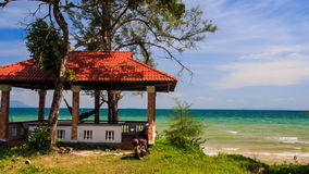 Red Roof Pavilion with Hammock on Beach against Azure Sea. Beautiful red roof pavilion with hammock on green lawn on beach against azure sea and skyline stock footage