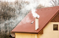 Red roof and smoking chimney. Smoking chimney on the red roof. Seasonal scene. Rural house Stock Photo