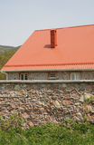Red roof and stone fence Stock Photo