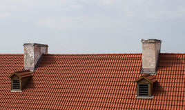 Red roof and two chimney against the sky Stock Photography