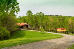 A red-roofed barn on the farm in the spring. royalty free stock photos