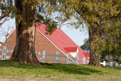 Red-Roofed Colonial Building. Brick building with dormers and red roof in rural setting Stock Photography
