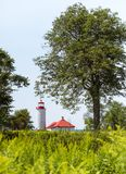 A red roofed lighthouse framed by trees stock photos