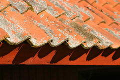 Red roofing tiles. Array of red roofing tiles with moss on them, resting on a red beam. Roof of a Swedish barn Royalty Free Stock Images