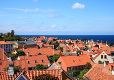 Red roofs and ocean at Gudhjem town in Denmark Stock Images