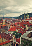 Red roofs under cloudy sky in Prague. Stock Photo