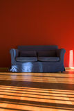 Red room with blue sofa Stock Images