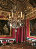 Red room with large paintings and chandelier at Versailles Palace, France Royalty Free Stock Image