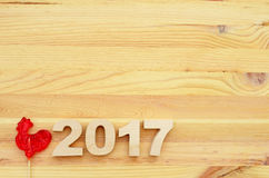 Red rooster, symbol of 2017 on the Chinese calendar. Lollipop in the form of a red rooster on a wooden background royalty free stock photography