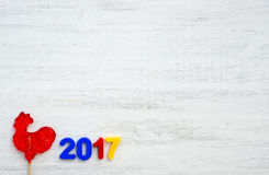 Red rooster, symbol of 2017 on the Chinese calendar. Lollipop in the form of a red rooster on a wooden background stock photo