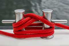Red rope fasten on stake of yacht Stock Photo