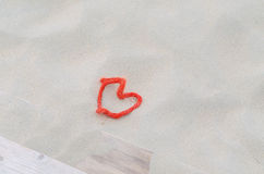 A red rope in heart shape in the sand. Stock Photo