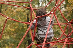 Red ropes. Little boy is playing on a playground with red ropes Stock Image