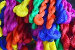 Red ropes, blue, yellow, pink, orange are tied together. stock image