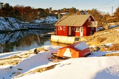 Red rorbu on rocky coast, around rocks covered with snow Royalty Free Stock Images