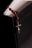 Red rosary and holy bible. Shot with dramatic lighting Stock Photos