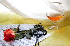 Red rose. Beautiful red rose with music notes, glass and bijoux Royalty Free Stock Image