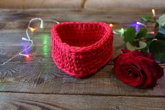 Red rose with a basket in the form of a heart and lights as a gift on a wooden background with copy space for text royalty free stock photos