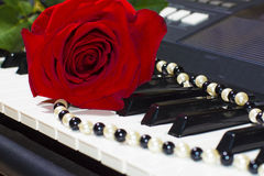 Red rose and bead on piano keys Royalty Free Stock Photos