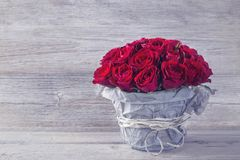 Red roses. Red rose in bicycle vase on a wooden background Royalty Free Stock Photos
