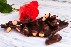 Red rose and black chocolate with hazelnuts royalty free stock images