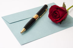 Red rose and black pencil on the blue envelope Royalty Free Stock Images