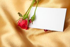 Red rose and blank card on golden satin Royalty Free Stock Photos