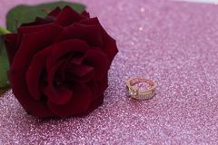 Red rose on blurred bokeh background, postcard for Valentine`s Day. Ring for betrothal. Fairy tale glitter bokeh background stock photography