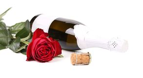 Red rose and a bottle of champagne. Royalty Free Stock Photography