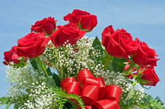 Red Rose Bouquet. Beautiful bouquet of a dozen red roses and white baby's breath against a blue sky background Stock Photo