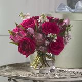 Red Rose bouquet. In a clear glass vase on a table with a package Stock Photos