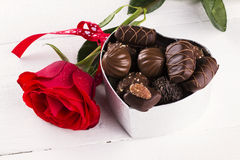 Red rose, box of chocolates on a white wooden background.  Royalty Free Stock Photography