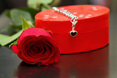 Red rose and bracelet Stock Photos
