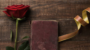Red rose, catalan flag and old book. A red rose, an old book and a catalan flag, on a rustic wooden table, for Sant Jordi, the Catalan name for Saint Georges Day Stock Photos