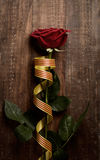 Red rose and catalan flag. A red rose and a catalan flag on a rustic wooden surface for Sant Jordi, the Catalan name for Saint Georges Day, when it is tradition Stock Images