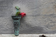 Red rose on cemetery. Vase of copper with withered red rose on a cemetery, Isle of Stromboli, Italy royalty free stock photo
