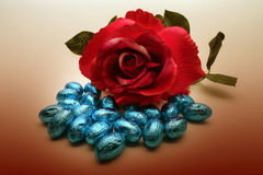 Red rose and chocolate eggs. Blue chocolate eggs and red rose background Stock Image