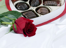 Red Rose and Chocolates. A deep red rose on white satin with open box of chocolates in background Stock Photo