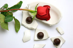 Red Rose and chocolates laying on a broken bowl Stock Image