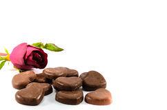 Red Rose and Chocolates. Red rose leaning towards some chocalate hearts Stock Photo