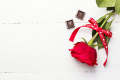 Red rose, chocolates on a white wooden background.  Royalty Free Stock Images