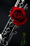 Red Rose On Clarinet. A red rose mounted on a Clarinet against a low key black background in the vertical format stock images