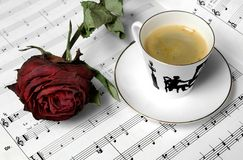 Red rose and coffeecup. On music paper Royalty Free Stock Image