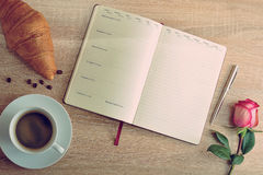 Red rose and a Cup of coffee with a croissant and diary with day Royalty Free Stock Photos