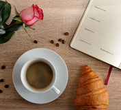 Red rose and a Cup of coffee with a croissant and diary with day Stock Photo