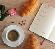 Red rose and a Cup of coffee with a croissant and diary with day Royalty Free Stock Images